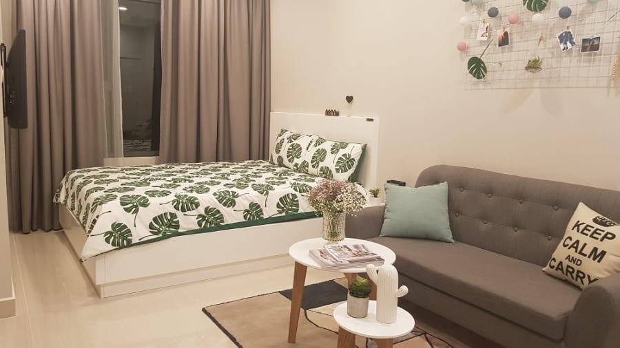 Sát giường ngủ là khu vực tiếp khách được chia khu nhờ chiếc thảm trải sàn.
