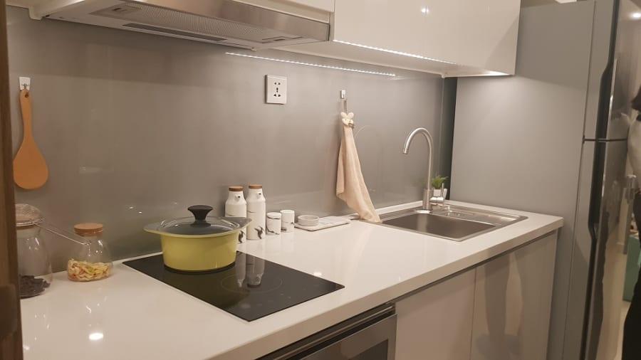 Mặt đá bóng kính màu trắng làm cho gian bếp càng thêm đẹp mắt